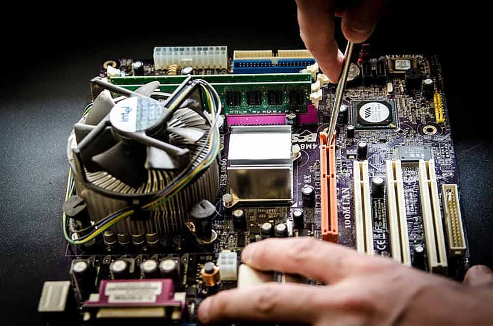 person-holding-screw-fixing-multicolored-computer-motherboard-low-res